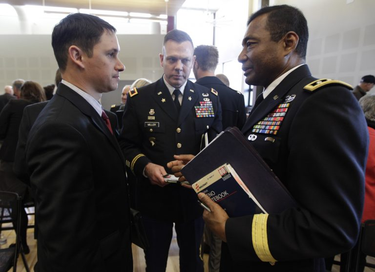 John Millan, (left), a 17-year member of the Washington Army National Guard who was diagnosed with PTSD in 2005 after serving in Iraq, talks with U.S. Army Lt. Gen. Thomas Bostick, (right), deputy chief of staff, G-1, as Col. Mike Miller, (center), looks on, following a field hearing of the U.S. Senate Veterans' Affairs Committee, Wednesday, April 4, 2012, in Tacoma, Wash. (Ted S. Warren/AP Photo)