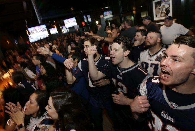 Coleman Hands, center, of Dallas, Davis Smith, second from right, of Austin, Texas, and Brian Moran, right, of Boston cheer while watching the first half of the NFL Super Bowl 52 football game between the New England Patriots and the Philadelphia Eagles in Minneapolis, Sunday, Feb. 4, 2018. (AP Photo/Steven Senne)