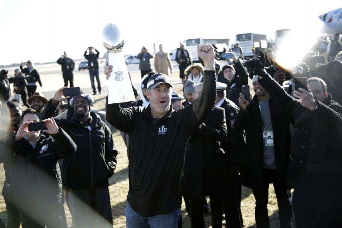 Eagles head coach Doug Pederson holds up the Vince Lombardi Trophy while displaying it to fans gathered to welcome them in Philadelphia a day after defeating the New England Patriots in Super Bowl 52 in Minneapolis, Monday, Feb. 5, 2018. (AP Photo/Julio Cortez)