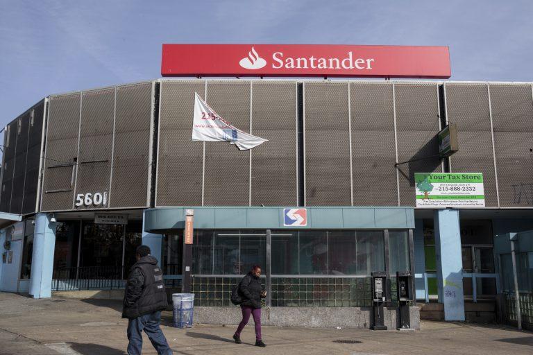 pedestrians pass a now-closed Santander Bank branch in Philadelphia.