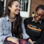 Rachelle Faroul, right, and her partner, Hanako Franz, sit outside their new home in Philadelphia