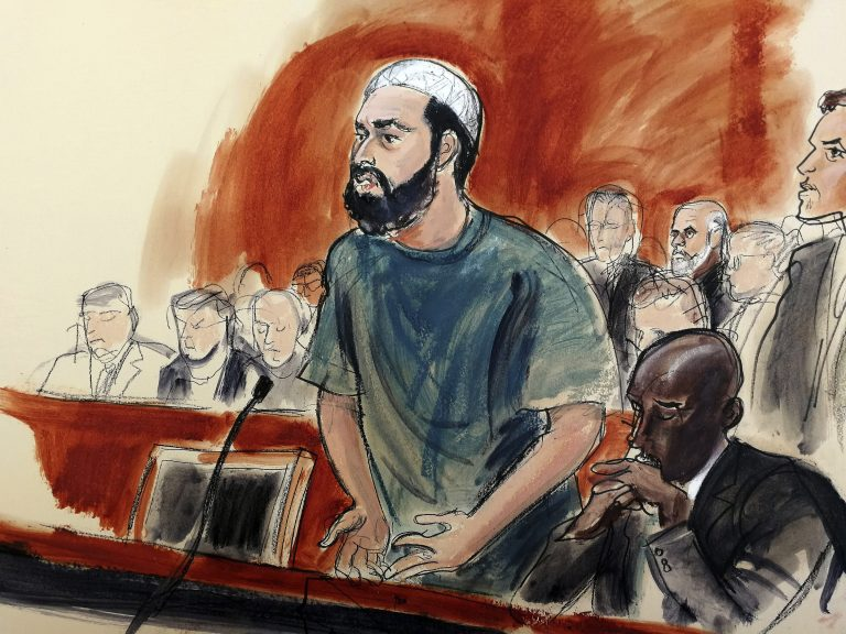 In this courtroom drawing, defendant Ahmad Khan Rahimi reads a statement to the judge during his sentencing hearing in New York, Tuesday, Feb. 13, 2018. Rahimi was sentenced to multiple terms of life in prison for setting off small bombs in two states, including a pressure cooker device that blasted shrapnel across a New York City block. At right is attorney Xavier Donaldson, Rahmin's attorney. (Elizabeth Williams via AP)
