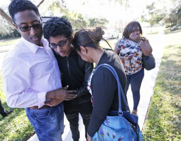 Family members embrace after a student walked out from Marjory Stoneman Douglas High School, Wednesday, Feb. 14, 2018, in Parkland, Fla. The shooting at the South Florida high school sent students rushing into the streets as SWAT team members swarmed in and locked down the building. Police were warning that the shooter was still at large even as ambulances converged on the scene and emergency workers appeared to be treating those possibly wounded.