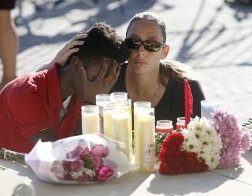 Pamela Tilton, (right), comforts Che James-Riley, 18, as they light a candle at a memorial for the victims of the shooting at Marjory Stoneman Douglas High School, Thursday, Feb. 15, 2018, in Parkland, Fla. (Wilfredo Lee/AP Photo)