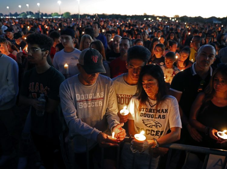 Jorge Zapata, Jr., center, a student at Marjory Stoneman Douglas High School, holds candles with his mother Lavinia Zapata, and father Jorge Zapata, Sr., during a candlelight vigil for the victims of the Wednesday shooting at the school, in Parkland, Fla., Thursd