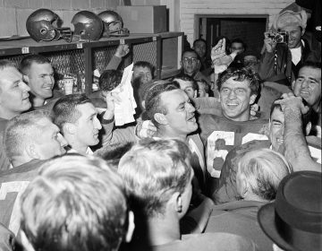 Norm Van Brocklin, left, who quarterbacked the Philadelphia Eagles to a 17-13 win over the Green Bay Packers in 1960, alternately laughs and cries in dressing room at Franklin Field. With him is Chuck Bednarik. (AP photo)