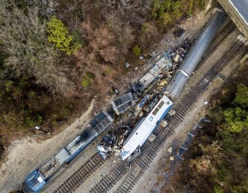 An aerial view of the site of an early morning train crash Sunday, Feb. 4, 2018 between an Amtrak train, bottom right, and a CSX freight train, top left, in Cayce, SC. The Amtrak passenger train slammed into a freight train in the early morning darkness Sunday, killing at least two Amtrak crew members and injuring more than 110 people, authorities said.  (Jeff Blake/AP Photo)