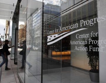 """A man walks into the Center for American Progress, Wednesday, Feb. 21, 2018, at their office in Washington. The major liberal policy group is raising the ante on the health care debate with a new plan that builds on Medicare to guarantee coverage for all. Called """"Medicare Extra for All,"""" the proposal to be released Feb. 22, 2018, by the Center for American Progress gives politically energized Democrats more options to achieve a long-sought goal. (Jacquelyn Martin/AP Photo)"""