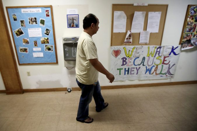 In this Oct. 12, 2017 photo, Arthur Jemmy walks through a hallway at The Reformed Church of Highland Park, where he and his wife are taking sanctuary to avoid deportation in Highland Park, N.J. The church, who is led by pastor Seth Kaper-Dale, who has a history of hosting immigrants in danger of deportation. A federal judge on Friday, Feb. 2, 2018, has temporarily halted deportation proceedings against Indonesian Christians who are in the U.S. illegally but are seeking to gain legal status. (Julio Cortez/AP Photo)