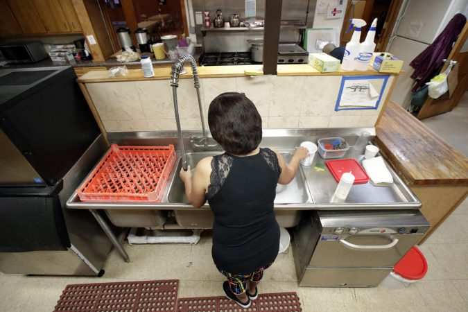 In this Oct. 12, 2017 photo, Silfia Jemmy, who is taking sanctuary to avoid deportation along with her husband, Arthur, at The Reformed Church of Highland Park, washes dishes in the church's kitchen in Highland Park, N.J. The church, who is led by pastor Seth Kaper-Dale has a history of hosting immigrants in danger of deportation.  A federal judge on Friday, Feb. 2, 2018, has temporarily halted deportation proceedings against Indonesian Christians who are in the U.S. illegally but are seeking to gain legal status. (Julio Cortez/AP Photo)