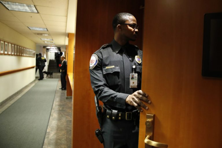 A security guard checks inside of a meeting room after it was evacuated by police with the Department of Homeland Security, where the Federal Communications Commission (FCC) was about to vote on net neutrality, Thursday, Dec. 14, 2017, in Washington. The room was shortly declared to be safe and the meeting continued where the FCC voted along party lines to repeal net neutrality. (Jacquelyn Martin/AP Photo)