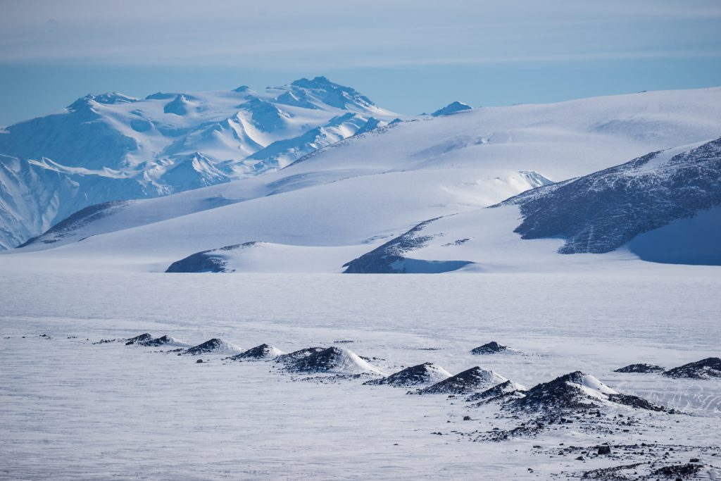 Mountains in Antarctica are covered in white powdery snow.