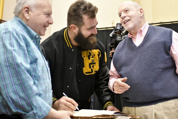 Alumni and volunteers Chuck Steinburg (left) and David Kahn (right) share the history of the guestbook as Philadelphia Eagles center Jason Kelce leaves his signature. The entries in Central High's guestbook date back to 1838 and include two presidents as well as other notable alumni. (Bastiaan Slabbers/for WHYY)
