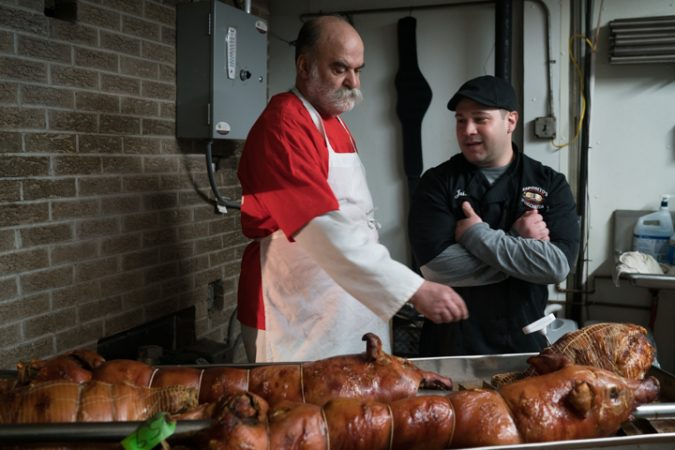 Sid Dk and Jules Esposito keep an eye on the freshly cooked pork at Esposito's Porchetta in South Philadelphia before the Super Bowl on January 4, 2018. (Branden Eastwood for WHYY)