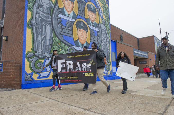 Marchers pass the 35th Police District in the Olney section of the city. (Jonathan Wilson for WHYY)