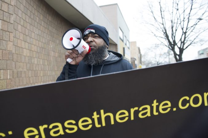 Radio personality Ikey Raw encourage passers by to join the march. Jonathan Wilson for WHYY)