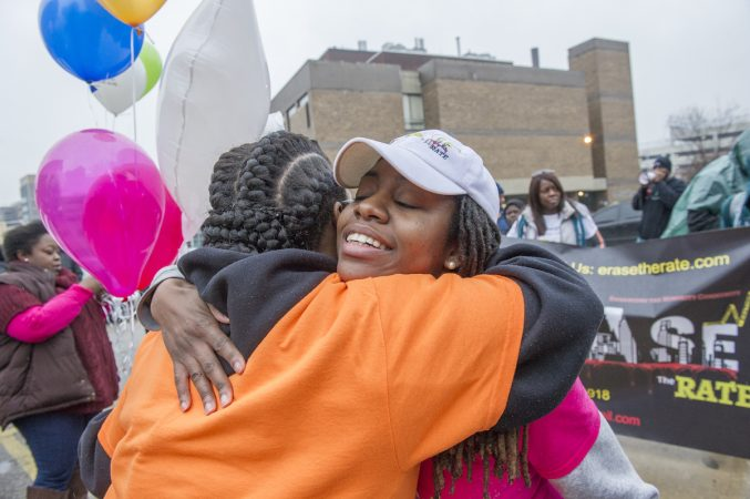 Mothers Bonded by Grief member Johndell Gredic, left, embraces Erase the Rate founder Davida Garner in the parking lot of the Philadelphia Medical Examiner's office. (Jonathan Wilson for WHYY