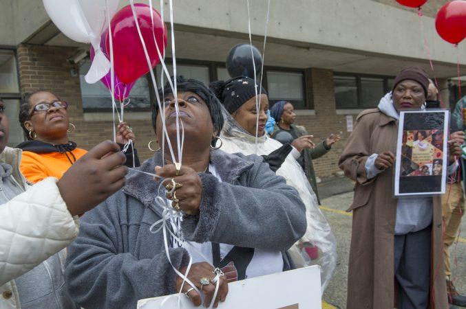 Diane Williams, whose 22 year old son Howard Williams was murdered prepares to release balloons in his honor. (Jonathan Wilson for WHYY)