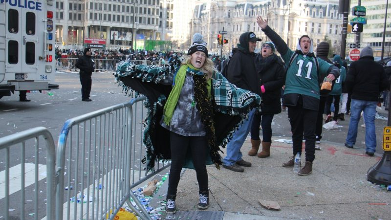 Long after the parade has passed, Brittany Robinson of Conshohocken screams her support for the Eagles. (Emma Lee/WHYY)