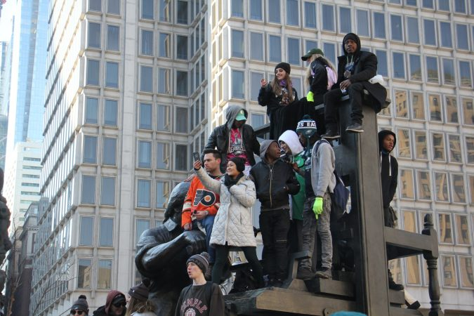 Eagles fans perch on a statue in Thomas Paine Plaza, watching the Super Bowl celebration on a jumbotron. (Emma Lee/WHYY)