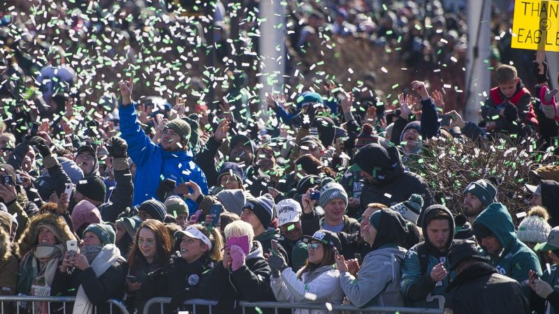 Fans are showered with confetti from passing team buses. (Jonathan Wilson for WHYY)