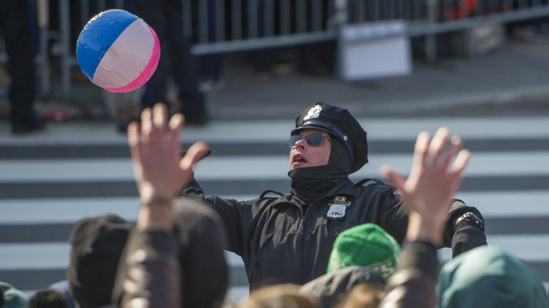 A police officer passes a beach ball back to the crowd. (Jonathan Wilson for WHYY)