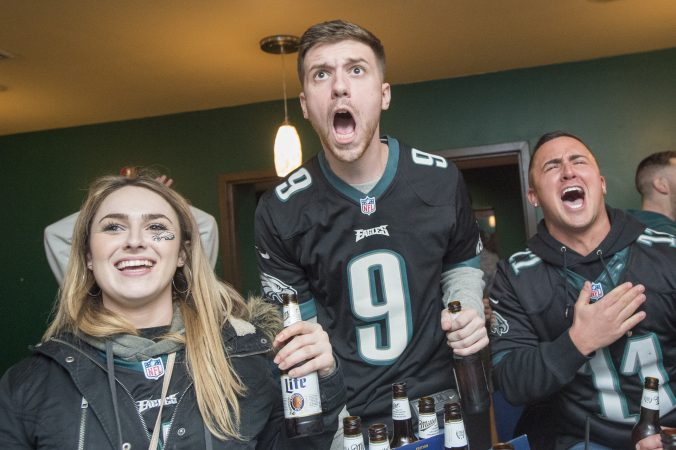 At Jon's Bar & Grille, patrons cheer as the Eagles score early in the game.