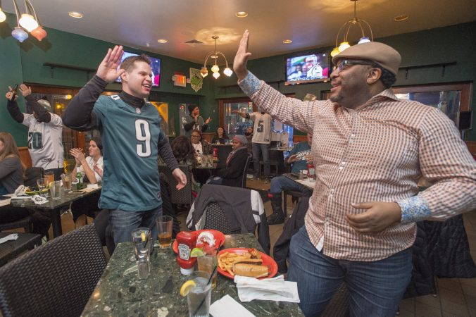 Eric Yoder, left, and Raymond Jones high five at Jon's Bar & Grille as Eagles score a touchdown.