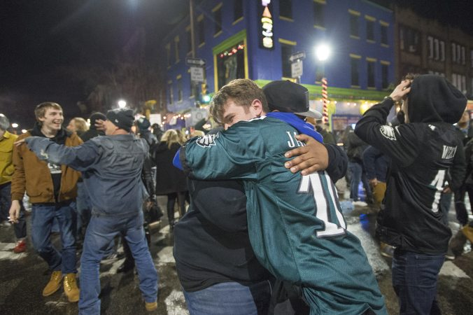 Eagles fans embrace at Fourth and South Streets.