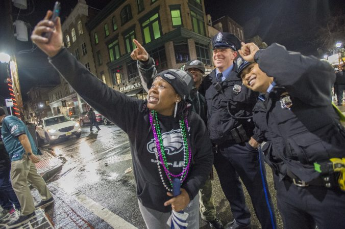 A woman takes a selfie with Philadelphia Police officers.