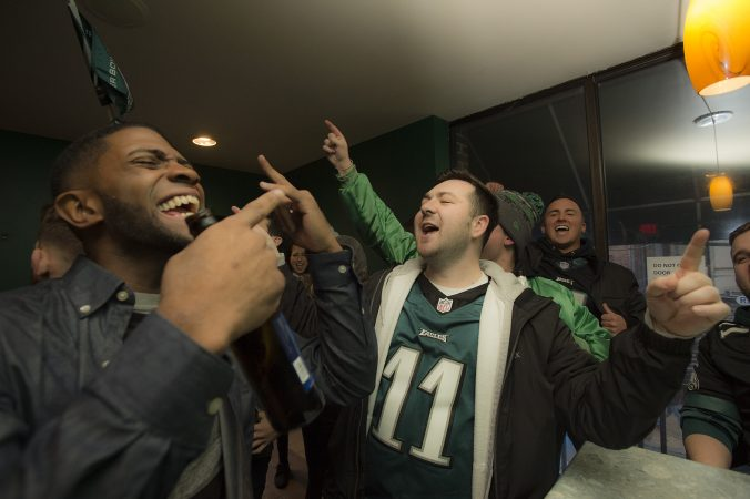 Eagles fans at Jon's at 3rd and South Streets cheer the team hours before the Super Bowl begins.