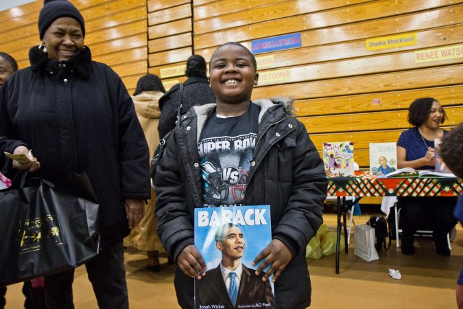 Semaj Scott, 7, likes books about history and sports. His grandmother, Juanita Scott looks on at the 26th annual African-American Children's Book Fair at the Community College of Philadelphia. (Kimberly Paynter/WHYY)
