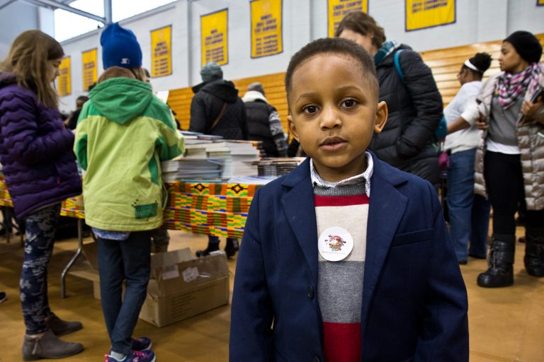 Ellis McGruder Jr., 4, and his dad attended the 26th annual African-American Children's Book Fair at the Community College of Philadelphia. They are starting a YouTube channel to post videos of them reading together. (Kimberly Paynter/WHYY)