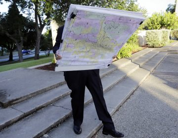 A man with a set of maps heads to a federal courthouse in San Antonio last year for a redistricting trial. Texas is one of three states with cases before the Supreme Court in redistricting. (Eric Gay/AP)