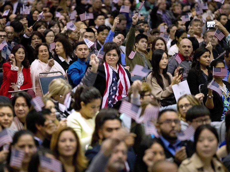 People wave U.S. flags during a 2017 naturalization ceremony at the Los Angeles Convention Center. (Jae C. Hong/AP)