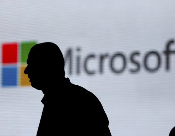An unidentified man walks in front of the Microsoft logo at an event in New Delhi, India. Microsoft is at the center of a Supreme Court case on whether it has to turn over emails stored overseas. (Altaf Qadri/AP)