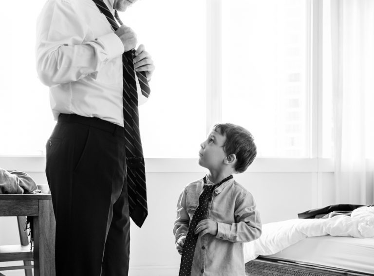 Father teaching the son how to tie a necktie