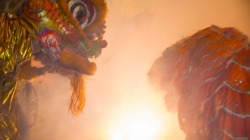 Members of the Philly Suns do a lion dance around a two-story string of firecrackers as they go off in celebration of the Chinese New Year in Phildelphia's Chinatown on February 15, 2018. (Emily Cohen for WHYY)