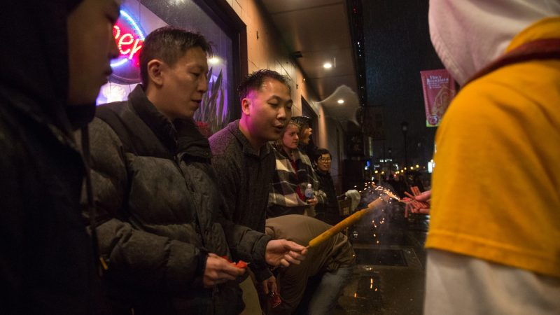 Older members of the community help the younger ones light their firecrackers during the downpour of rain that accompanied their celebration of the Chinese New Year in Phildelphia's Chinatown on February 15, 2018. (Emily Cohen for WHYY)