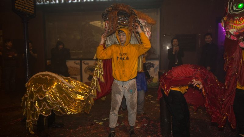 A member of the Philly Suns takes off his lion head after a sucessful lion dance through the streets of Chinatown in celebration of the Chinese New Year on February 15, 2018. (Emily Cohen for WHYY)