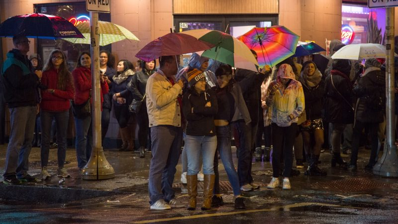 Dan Fogarty (center) and his wife Trish, stand and joke with family friend Angel Rodriguez, 20, as they wait for the lion dances to begin in celebration of the Chinese New Year in Phildelphia's Chinatown on February 15, 2018. (Emily Cohen for WHYY)