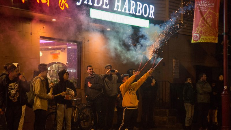 Matt Hing, 15, (center) lights off 4 firecrackers at once in celebration of the the Chinese New Year in Phildelphia's Chinatown on February 15, 2018. (Emily Cohen for WHYY)