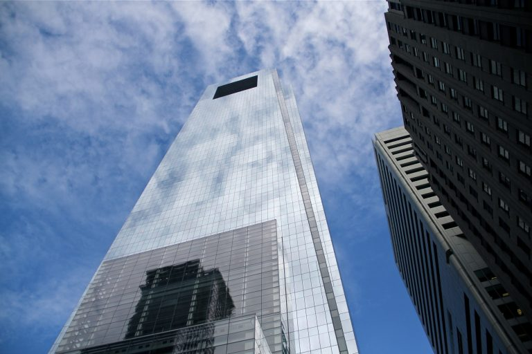 The Comcast tower in Philadelphia reflects clouds and blue sky.