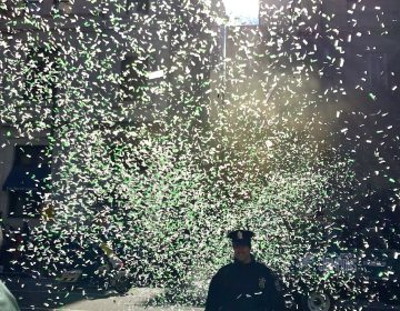 Philly police office grinning and shrouded in green confetti