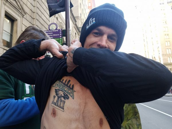 Jason Yurchak lifts up 13 layers of clothing to show his new Eagles Super Bowl Championship tattoo.