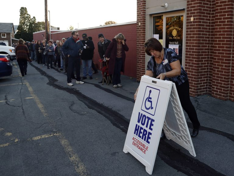 An election official places a sign as voters line up outside a polling place November 2016 in Fogelsville, Pa. (AP Photo/Matt Slocum)