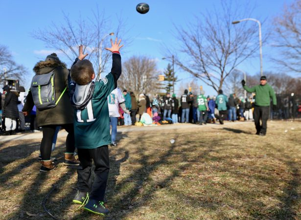 Grant DeCosta throws a spiral to his son, Luke, 8, as they wait to greet Super Bowl Champions: the Philadelphia Eagles.