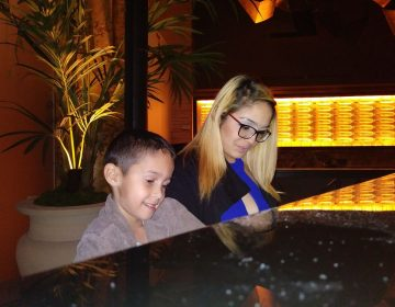 Muriel Rivera and her son Yeriel playing the piano at the hotel where she's been staying since November.