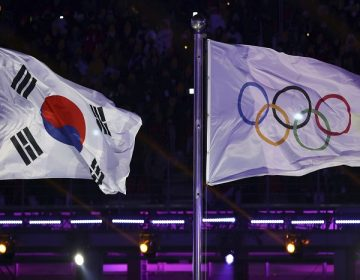 The South Korea and Olympic flag are seen during the opening ceremony of the 2018 Winter Olympics in Pyeongchang, South Korea, Friday, Feb. 9, 2018. (AP Photo/Michael Sohn)