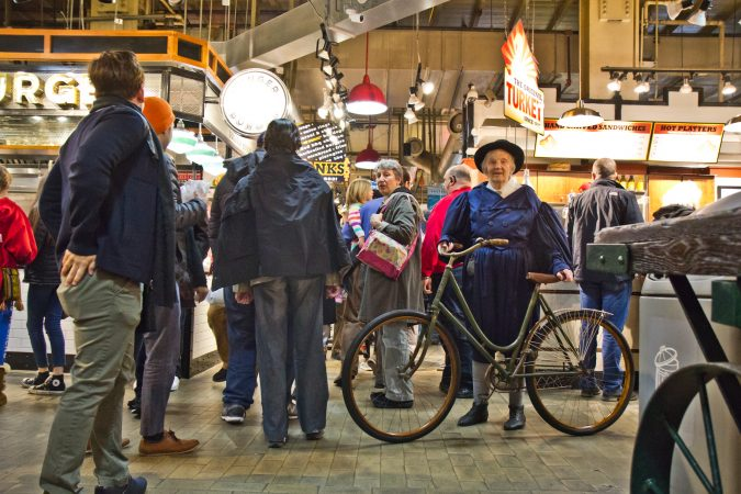 Sue Gray of the Wheelman Antique Bike Club shows off her bike at the Reading Terminal Market 125th anniversary celebration. (Kimberly Paynter/WHYY)